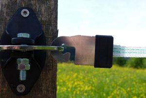 Litzclip Torgriffverbinder am Isolator an einem Weidezaunpfahl.